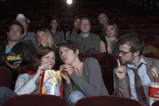 Girls talking in movie theater.